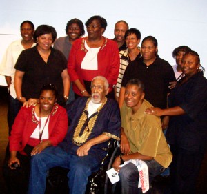 Kwame McDonald, seated front center, with members of the Summit-University Stars women's basketball team he founded and coached Photo by Charles Hallman