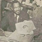 Paul Robeson, star of Shakespeare's Othello, now playing at the Orpheum Theater, takes time out between shows to autograph copies of his own recordings of Shostakovich's United Nations, which will be sold here for the benefit of the Russian War Relief. Assisting Roberson is Mrs. R. W. Welch, fund secretary.