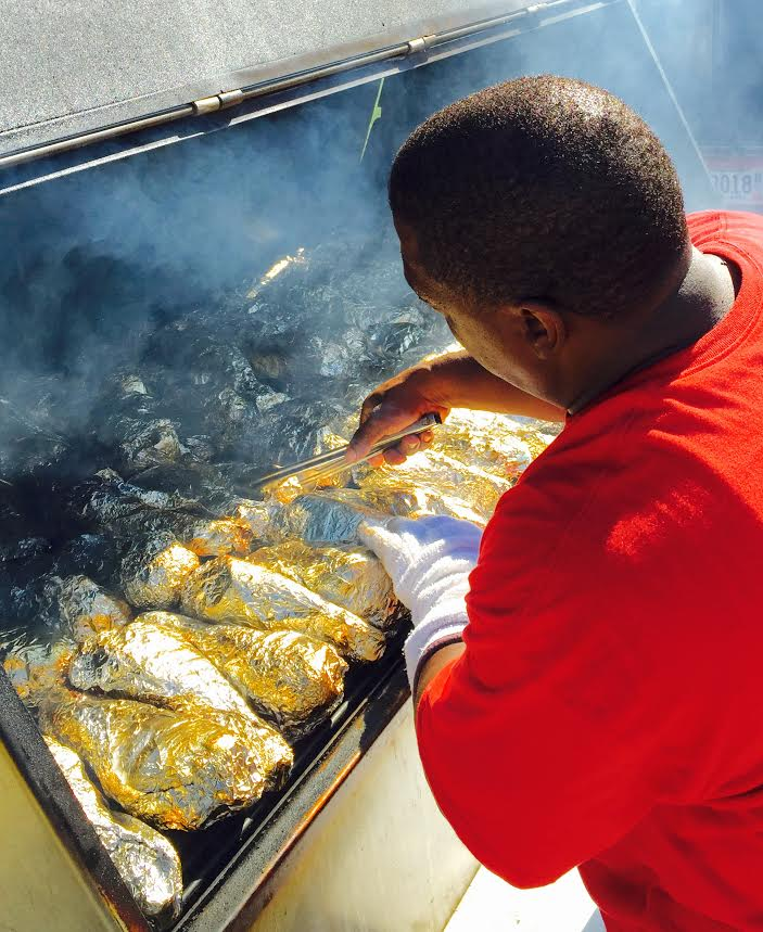 Brian White Sr. prepares turkey legs at Rondo Days