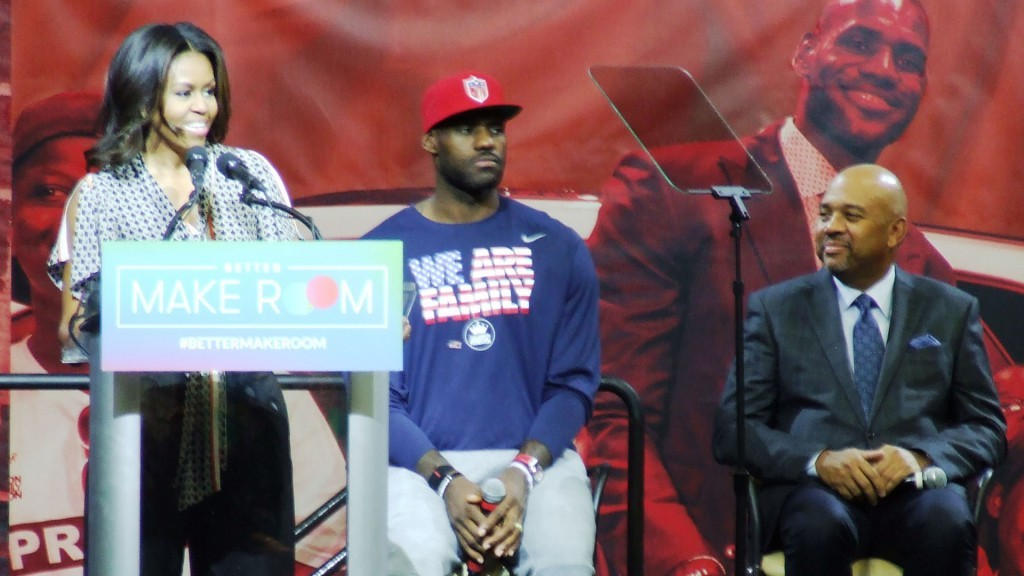 "First Lady Michelle Obama speaks to the audience about her ""Better Make Room"" Campaign at the University of Akron's James A. Rhodes (JAR) Arena on Wednesday, October 21, 2015 as NBA star LeBron James and ESPN Sports Commentator Michael Wilbon look on."
