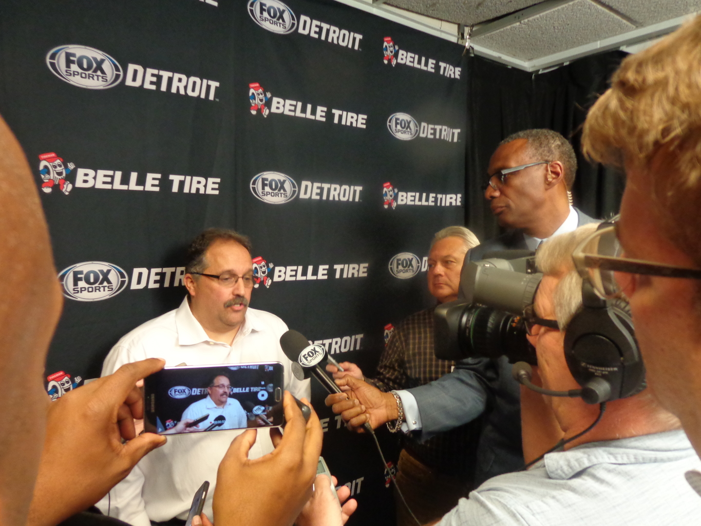 Pistons Coach Van Gundy, seated at left, is surrounded by reporters including Greg Kesler standing at right holding a Fox Sports mic.