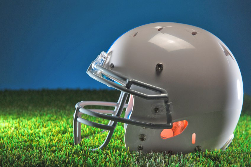 This is a photo of an American football helmet on green grass. The background bleeds to a dark blue.
