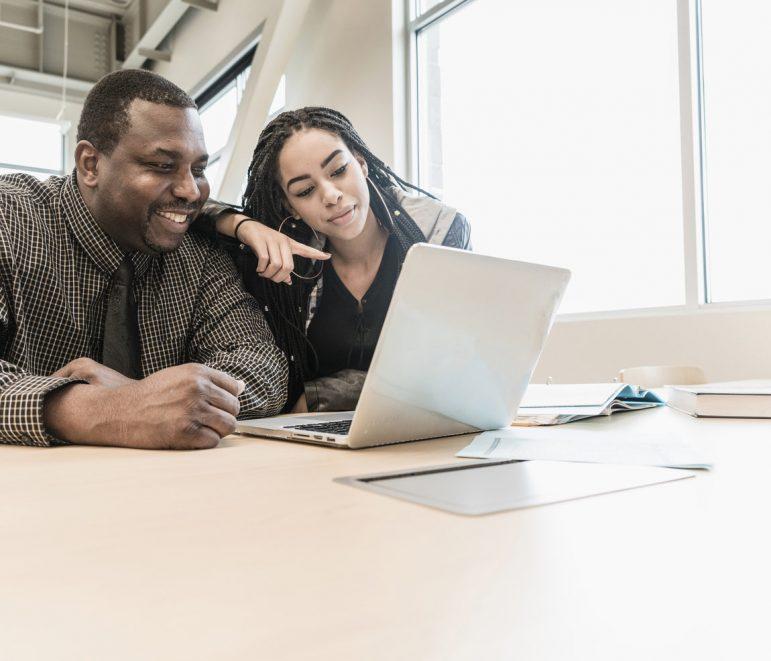Black teacher and student using laptop
